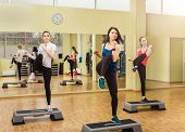 stock photo of step aerobics  - Group of young sportive women making step aerobics in the fitness class - JPG