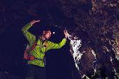 image of mystery  - Man walking and exploring dark cave with light headlamp underground - JPG