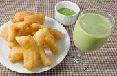 stock photo of dessert plate  - Snack and Dessert Chinese Traditional Snacks Deep Fried Doughstick on A White Plate Served with Pandan Custard Dip and Green Soybean Milk - JPG