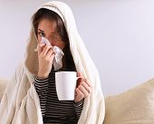 picture of sick  - Sick woman covered with blanket holding cup of tea sitting on sofa couch - JPG