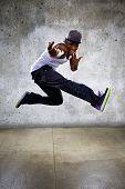 stock photo of parkour  - Black urban hip hop dancer jumping high on a concrete background - JPG