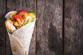 image of sandwich wrap  - Chicken wrap sandwich on wooden background with blank space - JPG
