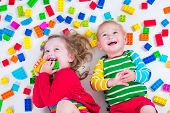 foto of twin baby girls  - Child playing with colorful toys - JPG