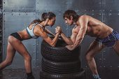 image of wrestling  - Athlete muscular sportsmen man and woman with hands clasped arm wrestling challenge between a young couple Crossfit fitness sport training lifestyle bodybuilding concept - JPG
