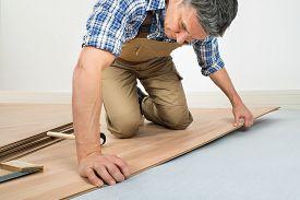 stock photo of laminate  - Carpenter Installing New Laminated Wooden Floor At Home - JPG