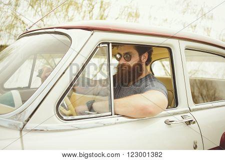 Bearded man behind the wheel of a retro car