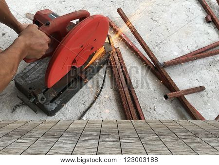 Man using steel cutters work and wood floor space for your product.