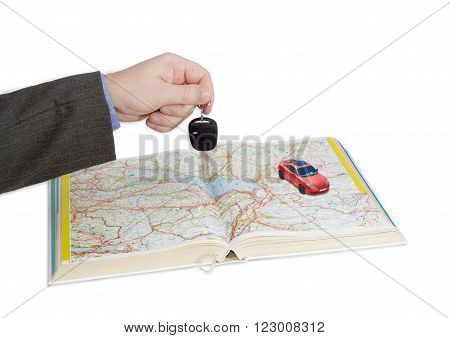 Male hand with car key over an open old road atlas and small red toy car on atlas on a light background