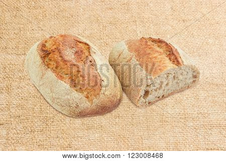 One whole loaf and one half loaf of wheat leavened bread with bran on a burlap