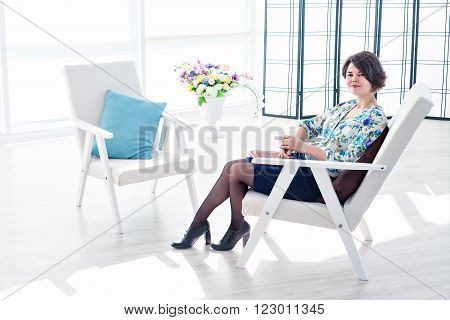 Portrait of a young woman psychologist therapist in a bright office. Beautiful modern space with an armchair for the client. Consulting psychologist in the office. A positive solution to the problems. Write in a notebook and reading a book in an armchair.