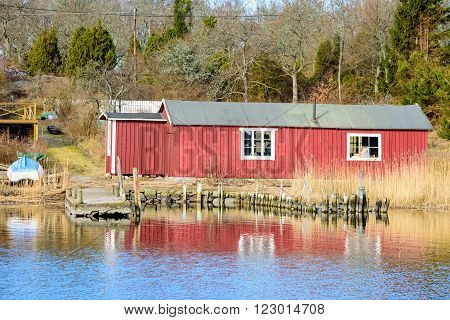 Torhamn Sweden - March 18 2016: A red wooden fishing shed with reed and pier outside. A small boat lies beside the shed up on land. Coastal woodland in background.