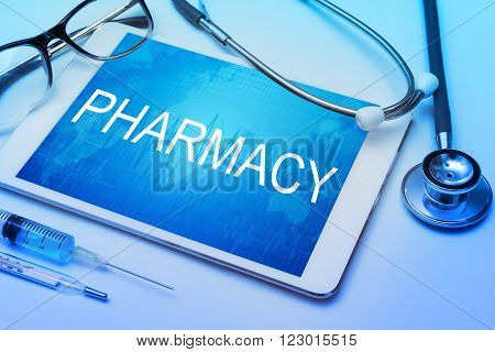 Pharmacy word on tablet screen with medical equipment on background