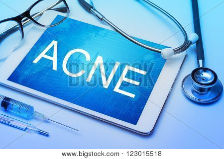 Acne word on tablet screen with medical equipment on background