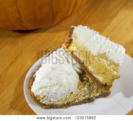 Two huge pieces of whipped pumpkin pie on a white plage