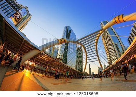 BANGKOK - Apr 21: Unidentified people walk along a skywalk in Sathorn on Apr 21, 2015 in Bangkok, Thailand. Home to international companies, Sathorn is the Thai capital's central business district.