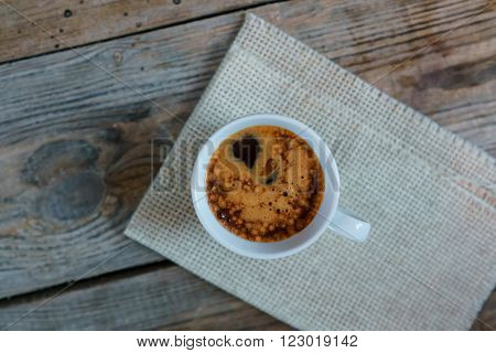 White cup of espresso crema on old wooden table. Cup of Espresso - stock photo.