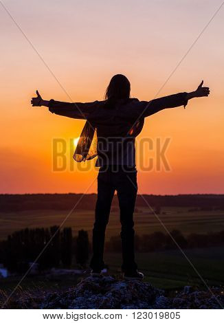 Silhouette of young longhair male model with thumbs-up hands at red and purple sunset sky.