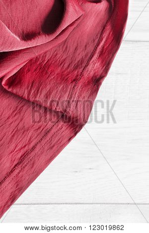 Red draped silk on white wooden background closeup