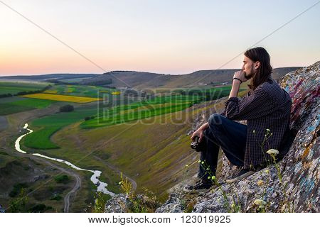 Handsome male model sitting on the rocks with dslr camera in hand above green fields and river.
