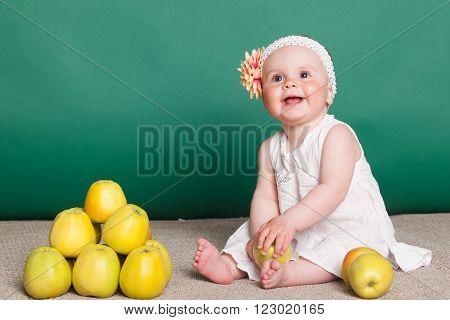 little nice girl with big yellow apples