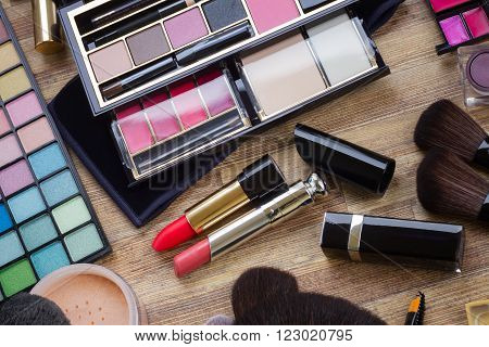 set of  brushes, lipsticks, maskara, eye shadows and  powder on wood