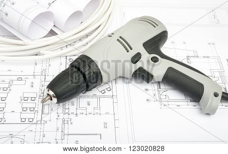 Architecture plan and rolls of blueprints with cabel and electric screwdriver. Building concept