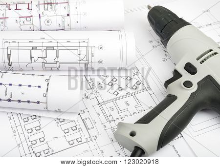 Architecture plan and rolls of blueprints with electric screwdriver. Building concept