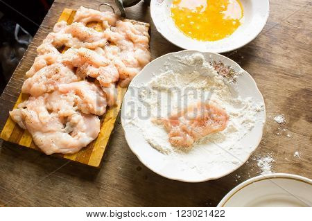 Many thin strips of chicken fillet prepared for cooking chops flour and beaten eggs in the plate