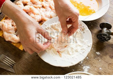 Hand dips a piece of chicken in flour for cooking chops