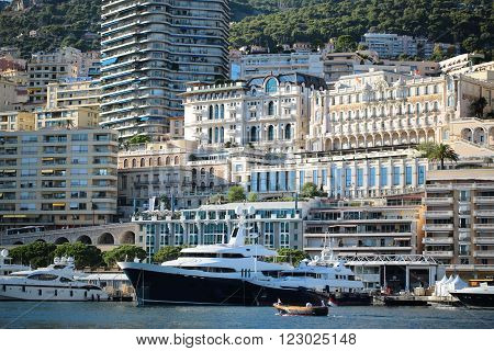 Monte Carlo Monaco - September 20 2015: yachts luxury large vessels ships at moorage in port and small motor boat inshore on sunny summer day on cityscape background horizontal picture
