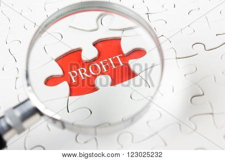 Profit concept. Magnifying glass searching missing puzzle peace.