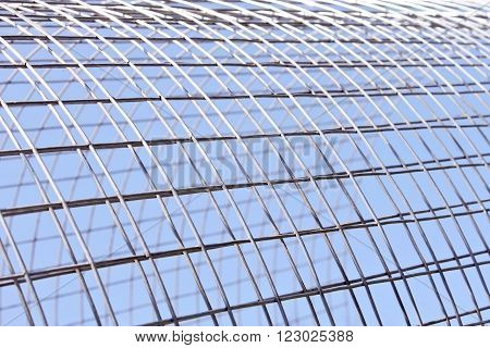 Metal grid of white alloy shines in bright sunlight on the blue sky background