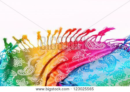 Colors of the rainbow bands on Indian fabric as a background. Rainbow gradient with a traditional pattern on stoles.  Isolation on a white background. The colors of the rainbow LGBT community. Brushes on the scarf. Symbol gay.