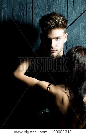 Young sensual couple of stylish man in shirt and pretty sexy topless woman with back embracing lover indoor on wooden background, vertical picture