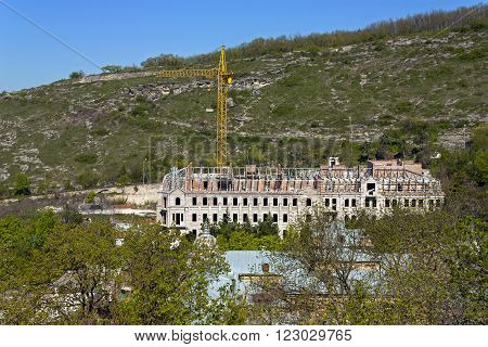 Construction concrete and red brick building under construction.