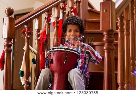 Smiling boy playing on drum. Young cheerful mulatto with drum. Let's here some traditional music. Talented djembe performer.