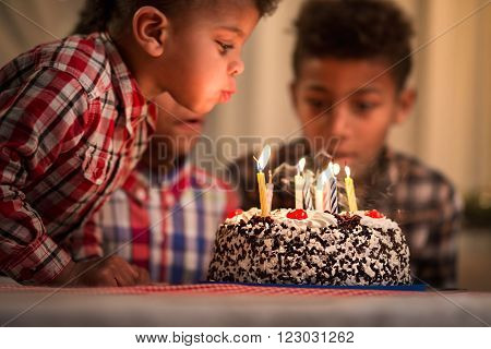 Black toddler blowing candles out. Child blows birthday candles out. Youngest brother's birthday. Spending festive time together.