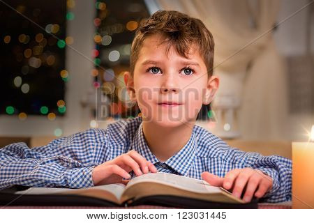Thoughtful child with a book. Kid with book near window. Waiting for a new idea. Holiday shall bring good thoughts.