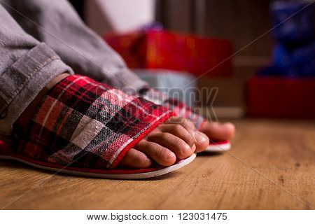Feet in slippers beside presents. Gift boxes beside child's feet. Morning surprise is waiting. What are you waiting for.