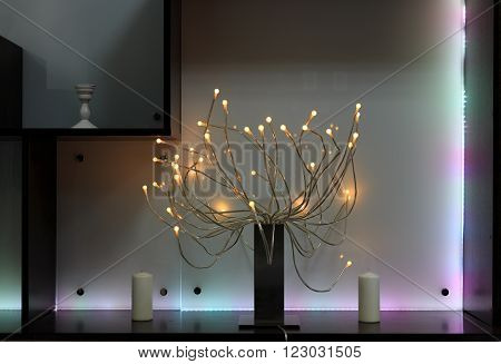 Shelf with lighting decoration led lamps tree and candes on black shelves against multicolor backlit plastic panel