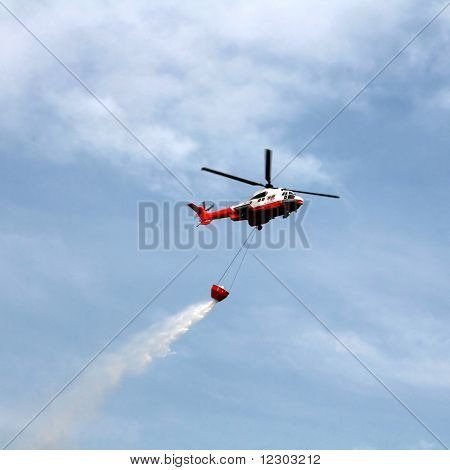 Fire fighting helicopter with bucket against blue sky