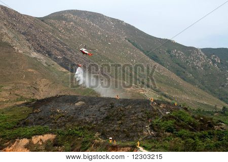 Fire fighting helicopter dousing burnt area of countryside