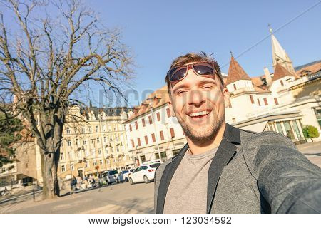 Young handsome man taking selfie at Meran old town in South Tyrol in Italy - Adventure and travel lifestyle around european destination - Composition with tilted horizon and warm afternoon color tones