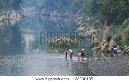 HA GIANG, VIETNAM - FEB 6, 2014: Vietnamese minority people washing clothes on the bank side of a river near their village.
