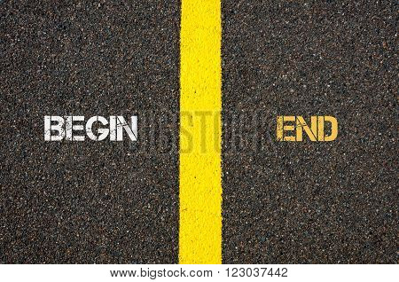 Antonym concept of BEGIN versus END written over tarmac, road marking yellow paint separating line between words