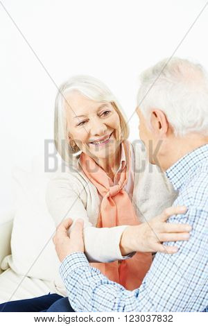 Old man and woman in love as a couple embracing at home