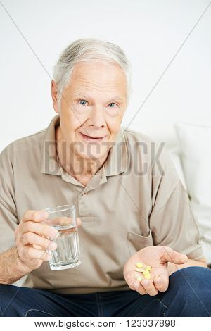 Senior man taking medicine with a glass of water