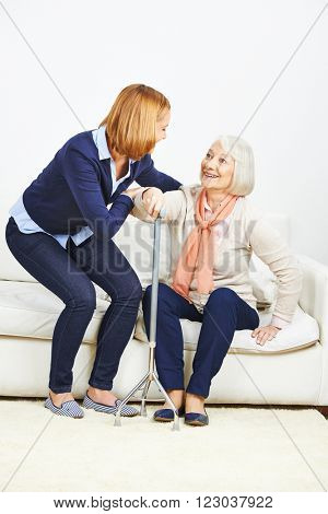 Woman helping senior woman with cane getting up from a sofa