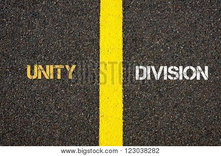 Antonym concept of UNITY versus DIVISION written over tarmac, road marking yellow paint separating line between words