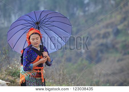 HA GIANG, VIETNAM - FEB 6, 2014: Unidentified Hmong woman holding her baby on back while walking home under the sunlight of spring.